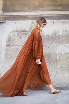 A rust coloured maxi dress is worn with beige pointed lace-up flats.