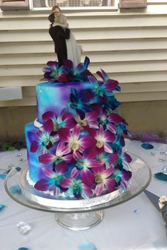 Wedding cake- two circle tiers -bright blue and purple color mix with blue and purple orchids on the cake - with a bride and groom cake topper
