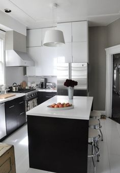 Find design inspiration in this tour of Amanda and Lincoln's eclectic modern home from Lindsay, of Apartment Therapy. This gourmet kitchen makes the most of the remodeled Victorian flat's limited floor plan by incorporating plenty of stylish storage options. The black kitchen island and white marble countertops are complemented by chrome accents and neutral gray walls.