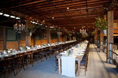 barn horse stall wedding banquet, long tables, glass chandelier, mixed flower bouquets in wood boxes, sonoma valley