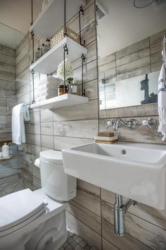 Rustic bathroom features a walk-in shower clad in wood like tiles lined with a teak folding shower bench as well as rain shower head over a grid tiled shower floor which continues to the rest of the bathroom finished with a seamless glass door.