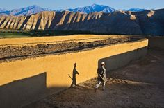 A brick worker in Bamiyan walks next to a wall.