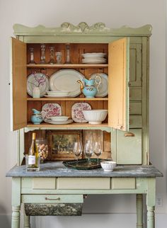 Most of the Hoosier cabinet's contents—like the whiteware platters and crystal candlesticks—came with the house.