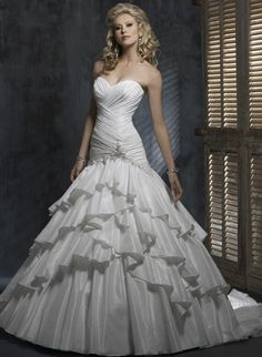 Full A-line gown with sweetheart neckline and corset closure. Tiers of fanciful frills will satisfy the princess within. Bordeaux Taffeta intersects throughout the bodice creating a marvelous woven look. Beaded embellishments outline the angular dropped waist.