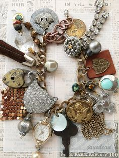 "Heirloom Trinkets Charm Bracelet -  vintage charms, buttons, beads and trinkets components are securely attached to brass chain that closes with a lobster clasp and copper extender.  Measurements:  Adjustable from 7"" to 8.5"" (17.8 cm to 21.6 cm)  Charms as long as 2.25"" (5.7 cm)"