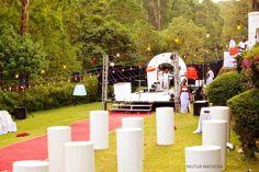 All white wedding decor in a lush green venue