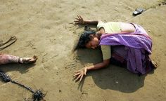 An Indian woman mourns the death of her relative (L) who was killed in the…