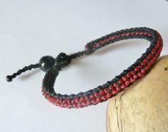 Schönes geknüpftes Armband in Makrameetechnik in schwarz, rot und pink.  Als Verschluss dient eine Holzperle, unser beliebter Schlaufenverschluss...