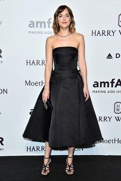 Dakota Johnson wears a black strapless Christian Dior dress, strappy heels, and black clutch