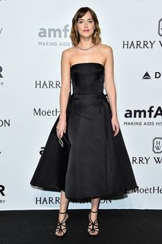 Dakota Johnson wears a black strapless Christian Dior dress, strappy heels, and black clutch