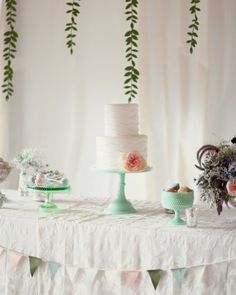 Use of the color in the cake stand and dishes....The Sweets    The dessert table, adorned with a pennant-flag garland and small flower arrangements, holds small treats including macarons and mini pecan pies. The piece de resistance: a two-tier cake -- zucchini lime with lime curd filling, and red velvet with cream cheese filling -- created by Intriciate Icings.