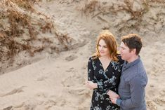 a red headed woman holding hands with her future husband posing for an engagement photoshoot with shoulder length hair wearing a knee length black dress with white flowers on a sandy beach in ireland Ireland Beach, Donegal, Shoulder Length Hair, Engagement Shoots, Future Husband, White Flowers, Red Hair, Holding Hands, Most Beautiful