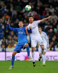 Xabi Alonso goes for a high ball against Samuel Martínez of Olimpic de Xativa during the Copa del Rey, Round of 32 2nd leg match between Real Madrid and Olimpic de Xativa at Santiago Bernabéu stadium on December 18, 2013 in Madrid, Spain.