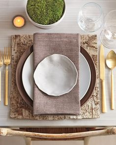 square wooden place mat . gold flatware . napkin under top dish . moss decoration