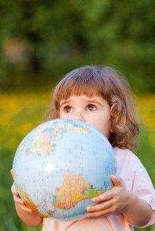 Little girl with a globe in a park