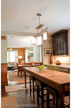 This perspective shows how Dutton was able to create a more open-concept kitchen, dining room and living room. Instead of a stationary island, she uses an antique nun's table on casters and easily stored bar stools for more flexibility in the kitchen.