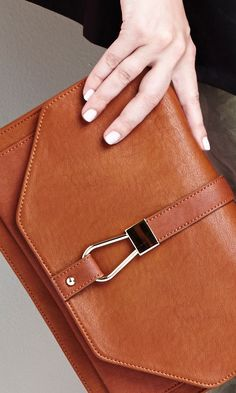 leather clutch with a boxy shape, fold over closure and metal hardware. Can also be worn as a crossbody bag thanks to the removable strap.