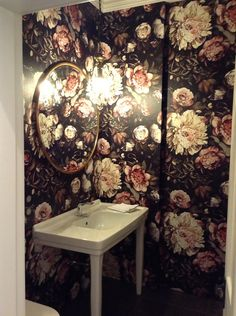 A dark floral jewel box of a powder room with dramatic, over-sized floral wallpaper by Ellie Cashman Design www.elliecashmandesign.com.