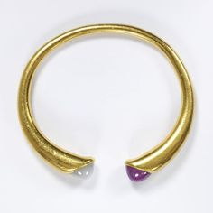 Archaeological style bangle by Fabergé, gold band with a star ruby and star sapphire at the terminal, workmaster August Hollming, 1908 - 1913.