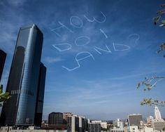 """La richiesta d'aiuto scritta con i gas di scarico nel cielo sopra Los Angeles è ovviamente una burla. L'ha organizzata Kurt Braunohler, comico di New York, attraverso la piattaforma  Kickstarter : """"Vi chiedo di donare soldi affinché possa ingaggiare un pilota per scrivere cose stu"""