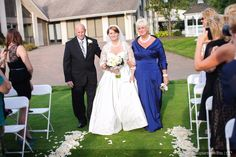 Bride walking down isle with mother and father during ceremony. Outside reception.