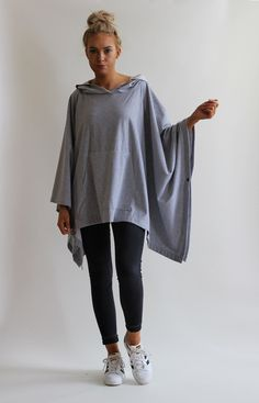 Oversized poncho in a grey marl cotton fabric with sporty kangaroo pocket and hood. Lightweight and comfortable to wear. One size fits UK 10-20. Our model is a size UK 10 and wearing this size.