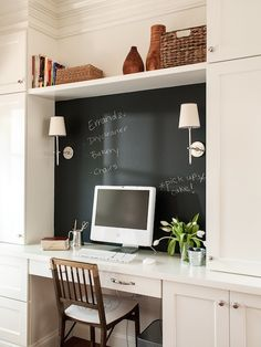 source: Lauren Liess Interiors Fabulous home office with wooden desk chair tucked under white built-in desk with chalkboard wall behind desk area lit with Thomas O'Brien Bryant Sconces below a floating shelf holding books, wooden vases and woven baskets.