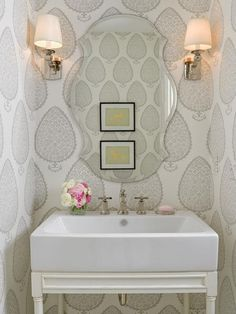 Pretty powder room features Katie Ridder Leaf Wallpaper on walls framing a scalloped beveled mirror flanked by a pair of polished nickel sconces with ivory shades over a French white sink console with trough sink.