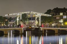 Magere Brug over the river Amstel illuminated at night, Amsterdam, North Holland. 400 Piece Puzzle. Magere Brug over the river Amstel illuminated at .