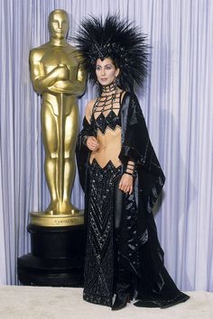 """When presenting the Best Supporting Actor award in 1986, Cher wore one of the most provocative Oscar outfits of all time: a midriff-bearing Bob Mackie getup featuring a beaded loincloth, a black cashmere cape, and a mohawk-style headpiece made of hundreds of rooster feathers (Cher had to sit on the floor of the limo on her way to the ceremony so as not to damage it). She is, said Mackie, """"an original.""""   - ELLE.com"""