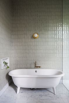 Simple modern bathroom with dove gray subway tile. marble floors and brass accents.