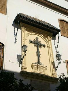 En la Calle Doña María Coronel, a pocos pasos de su intersección con Calle Gerona y sobre la fachada del Convento de las Hermanas de la Cruz, podemos ver esta hermosa y labrada cruz