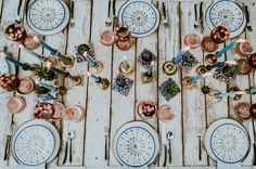 patterned plates // Southwestern spanish-inspired wedding tablescape with a rustic white farm table, blue colored candles and spanish tiles