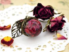 Handcrafted nature inspired real rose ring featuring beautiful rose bud encased in crystal resin ball and dangling brass leaf charm. The romantic