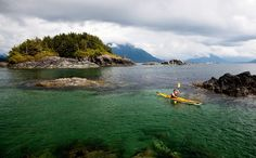 A sea kayaker explores the clear waters off Flores Island. Circumnavigating Vancouver Island might seem like child's play in comparison to circling an entire continent—which is why she recommends it as a great trip for budding expedition kayakers. Paddlers experience old-growth rain forests, empty Kayak