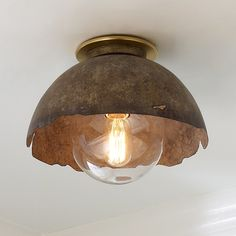 Eye-catching and intriguing, this ceiling light merges brutalist and industrial vibes with sleek modern sensibility. The shiny brass canopy and crystal clear glass globe dress up the worn bronze shade. The lacy distressed edge adds a subtly whimsical character that will help this high-style statement piece blend beautifully with found farmhouse and vintage decor, or more rugged rustic and industrial looks. Ceiling Light Shades, Ceiling Light Design, Semi Flush Ceiling Lights, Flush Mount Ceiling, Ceiling Light Fixtures, Lighting Shades, Ceiling Lighting, Rustic Flush Mount Lighting, Closet Lighting