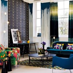the trickle down paint finish with the interesting choices of fabrics lend this living room a strong, graphic look