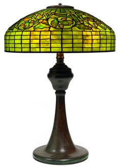 TIFFANY STUDIOS OAK LEAF TABLE LAMP  Bronze lamp base with green and yellow tiled domed shade in an oak leaf motif, circa 1910