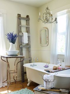 Think antiqued, romantic, and unexpected when selecting rustic bathroom decor. This bath benefits from a charming fusion of fine and functional forms. A chandelier with a verdigris finish and a rusted table with sinuous lines present feminine figures that contrast nicely with a primitive ladder employed as a towel rack.