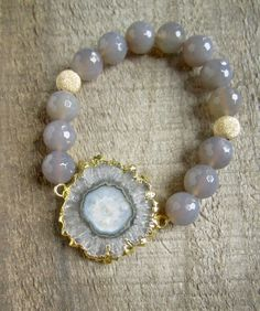 Natural stalactite is adorned with faceted gray chalcedony beads and punctuated with two glittering 14K gold fill stardust beads.
