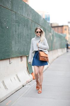 A denim skirt is the perfect piece to go along with the current '70s trend. Charlotte of The Fashion Guitar channels the retro style in a denim mini and cognac suede accessories. Perfect for seasonal transitions, this outfit also paired a denim skirt with a chunky sweater. Notice the masterful half tuck; it keeps the finished look ultra-flattering.
