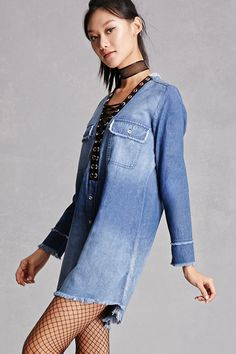 A denim shift dress featuring a lace-up neckline, button front, chest pockets with button flaps, long sleeves, and a frayed trim. This is an independent brand and not a Forever 21 branded item. (This item runs large, please size down.)