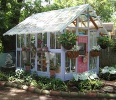 Greenhouse from old windows and doors. Mexican roofing tiles frame bed of liriope and hydrangea. www.karlaathome.com