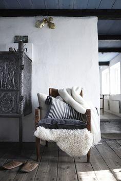 denim blue cushions, warm neutral tones, sheepskin, cream wool throws, wooden floor