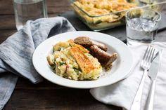 Recept voor ovenschotel voor 4 personen. Met zout, boter, olijfolie, peper, braadworst, aardappel, snijbonen, spekreepje, tijm, brie, ui en melk