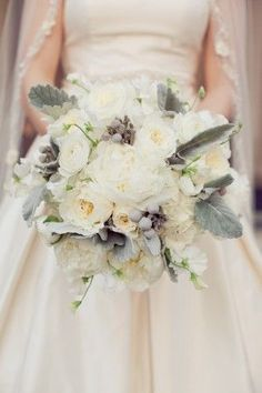 The bridal bouquet will be a clutch bouquet of cream hydrangeas, white peonies, white garden roses, ivory spray roses and white ranunuculus with grey dusty miller wrapped in ivory ribbon.