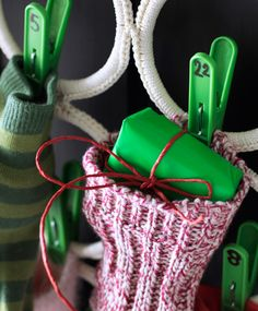A close-up of a sock filled with a present hanging from a clothes storage hanger using pegs.