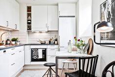 biała kuchnia nowoczesna z czarnymi blatami i krzesłami