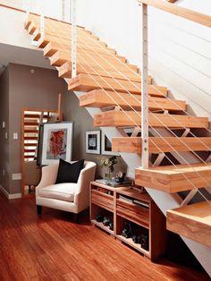 fauteuil, miroir et meubles sous escalier pour une entrée de maison chic