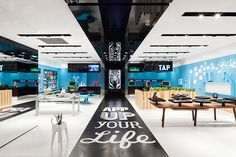 Following a black runway from the entrance, customers find the App Bar where they can try out mobile apps on a large interactive screen. Painted pegboards are used to cover the walls of the store.